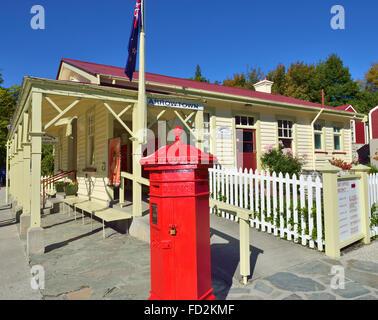 Une boîte aux lettres rouge devant l'ancien bureau de poste dans la rue principale de la ville , région de l'Otago flèche de l'île du sud de Nouvelle-Zélande.