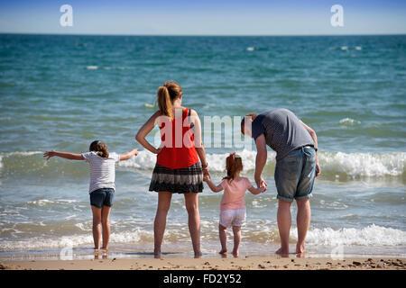 Un couple paddling avec leurs enfants sur la plage de Boscombe Bournemouth, Royaume-Uni
