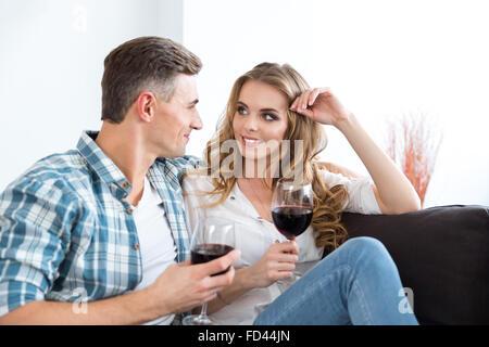 Couple heureux de parler et de boire du vin assis sur un canapé dans la chambre Banque D'Images