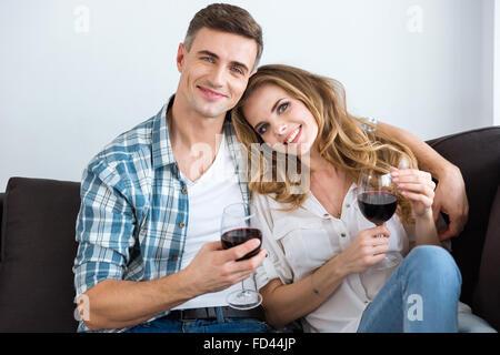 Beau couple sitting on sofa et boire du vin à la maison Banque D'Images
