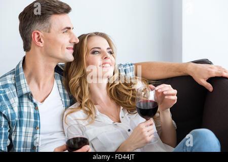 Heureux couple resting détendue et de boire du vin rouge sur la table à la maison Banque D'Images
