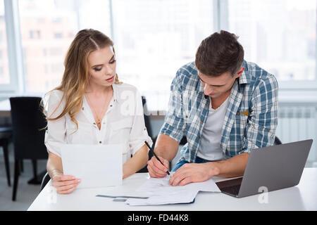 Concentrée pensive woman and man working et discuter de projet et à l'aide d'ordinateur portable dans le bureau Banque D'Images