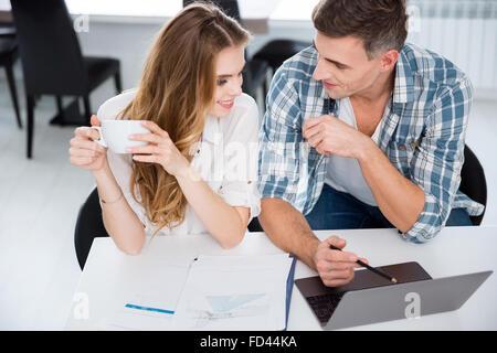 Heureux collègues assis dans le bureau et travailler avec laptop Banque D'Images