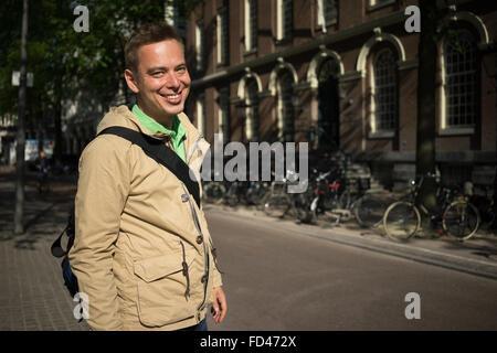 Beau jeune homme blond aux yeux verts souriant Voyager en Europe Banque D'Images