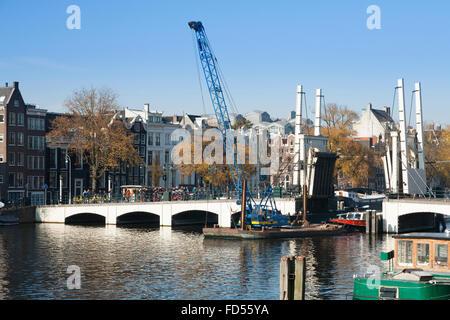 """Bateau / péniche passe sous le Magere Brug (pont """"Magere Brug"""") en Néerlandais Amsterdam, Pays-Bas, Hollande. Banque D'Images"""
