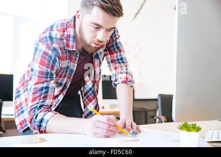 Bel homme concentré en chemise à carreaux et de travail plan de dessin avec mètre et crayon Banque D'Images