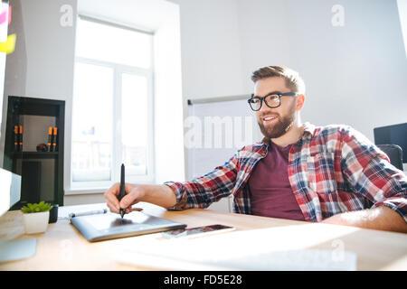 Smiling handsome young designer barbus en chemise à carreaux et des lunettes et de dessin à l'aide de la tablette Banque D'Images