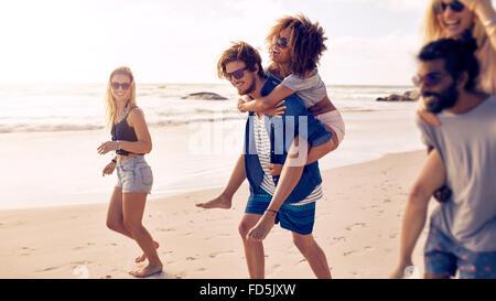 Deux jeunes hommes heureux en donnant leurs copines piggyback rides à la plage. Groupe d'amis, profiter de vacances à la plage.