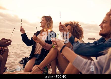 Groupe d'amis s'amusant avec les cierges magiques en plein air sur la plage. Groupe varié de jeunes célébrant le jour de l'an à th
