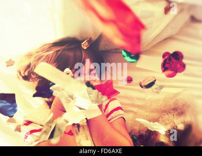 Girl Lying On Bed jetant Confetti et rire Banque D'Images