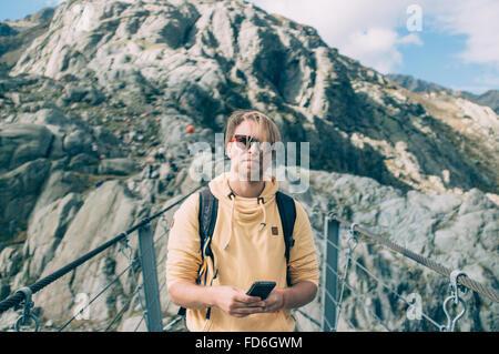 Jeune homme debout sur smartphone Avec Pont suspendu Banque D'Images