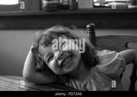 Happy Girl Faire face tout en étant assis sur une chaise Banque D'Images