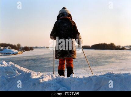 Vue arrière du Girl standing in Snow tenant des bâtons de ski Banque D'Images