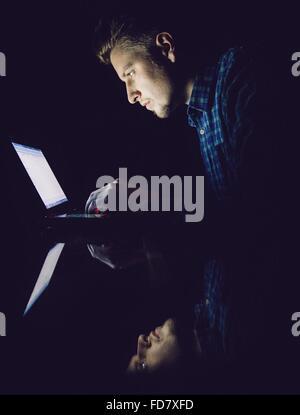 Reflet de jeune homme sur le verre pendant l'utilisation d'ordinateur portable en chambre noire