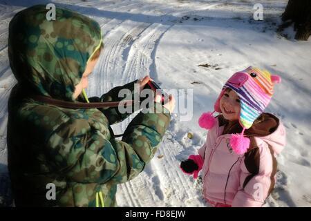 Frère Soeur photographier sur le terrain couvert de neige Banque D'Images