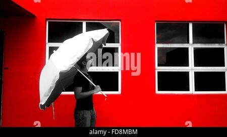 Man Holding Umbrella en face du bâtiment rouge Banque D'Images