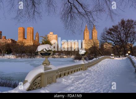 Central Park Bow Bridge au bord du lac et les bâtiments de l'Upper West Side à l'aube d'un matin d'hiver glacial. Banque D'Images