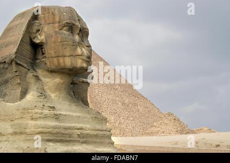 Le Sphinx garde les pyramides sur le plateau de Gizeh au Caire, Égypte. Banque D'Images