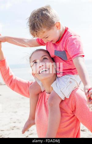 Jeune mère et son fils à la plage. Le petit garçon est sur ses épaules et les mères qu'ils sont à la recherche à Banque D'Images