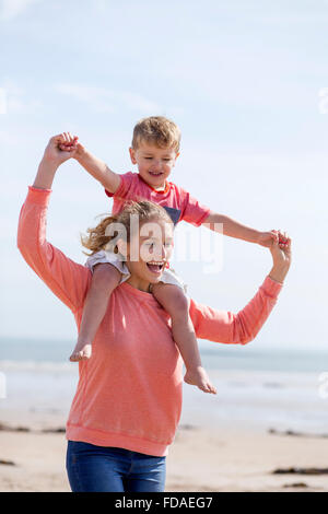 Portrait d'une jeune mère et son fils à la plage ensemble. Ils sont à la fois le sourire et le petit garçon est Banque D'Images