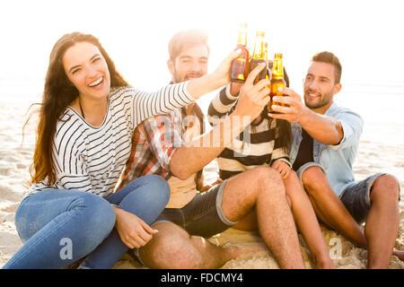 Les amis de s'amuser ensemble à la plage et de boire une bière froide Banque D'Images