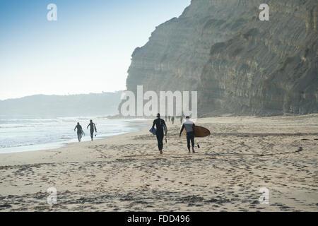 Marcher sur une plage de surfers avec leurs planches de surf Banque D'Images