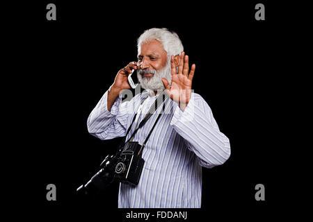 1 Senior Adulte indien caméraman parle Téléphone Mobile et part montrant Banque D'Images