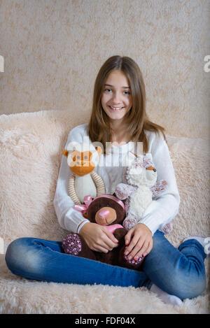 Avec des jouets de fille assise sur le canapé avec une couverture de fourrure