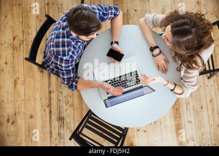 Vue de dessus du beau jeune couple parlant, à l'aide d'ordinateur portable et l'écran vide holding cell phone lors Banque D'Images