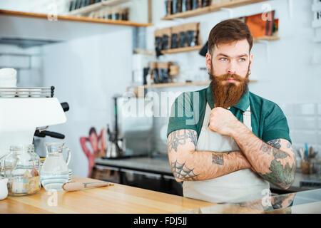 Beau santa claus barista de toucher sa barbe et la pensée in coffee shop