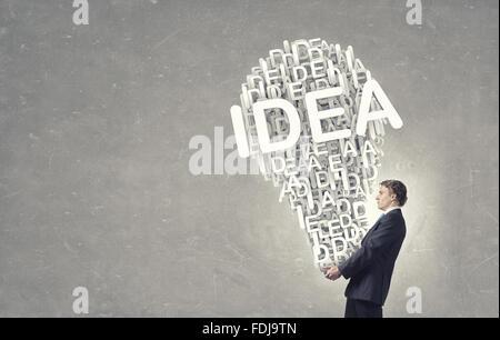 Young businessman carrying dans mains concept idée lampe Banque D'Images
