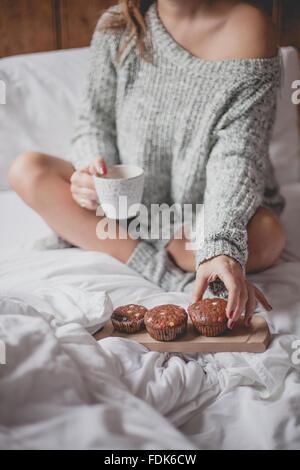 Femme assise sur le lit avec une tasse de thé et muffins Banque D'Images