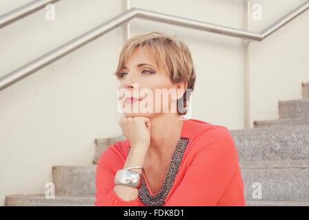 Femme assise sur l'escalier, la tête sur son menton Banque D'Images