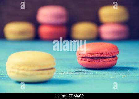 Certains macarons appétissants avec différentes couleurs et saveurs sur une surface en bois rustique bleu Banque D'Images