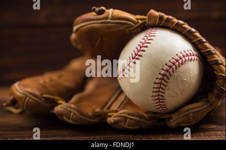Gant de baseball en cuir brun sur un banc en bois Banque D'Images