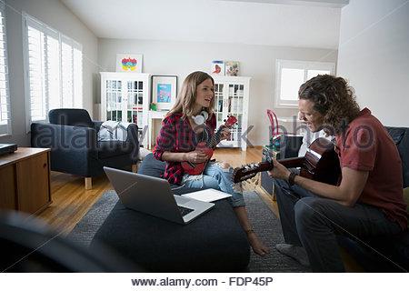 Couple qui joue de la guitare et ukulele in living room Banque D'Images