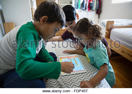 Mère et enfants jouant jeu sur tablette numérique Banque D'Images