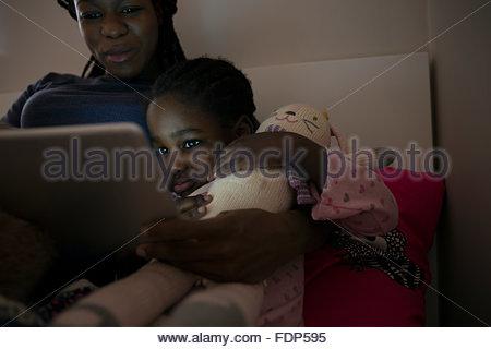Mère et fille à l'aide de tablette numérique à l'heure du coucher Banque D'Images