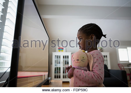 Fille avec poupée peluche regarder les dessins animés à plat Banque D'Images
