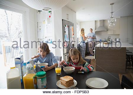 Famille en cuisine et manger le petit déjeuner Banque D'Images
