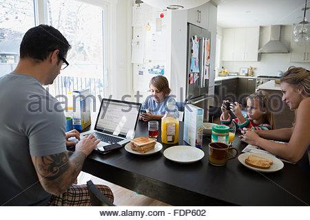 L'utilisation de téléphones cellulaires de la famille et l'ordinateur portable table de petit déjeuner Banque D'Images