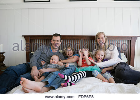 Riant Portrait family relaxing on bed Banque D'Images