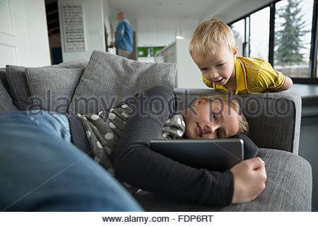 Frère et soeur regardant digital tablet on sofa Banque D'Images