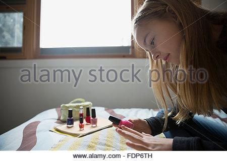 Girl painting fingernails on bed Banque D'Images