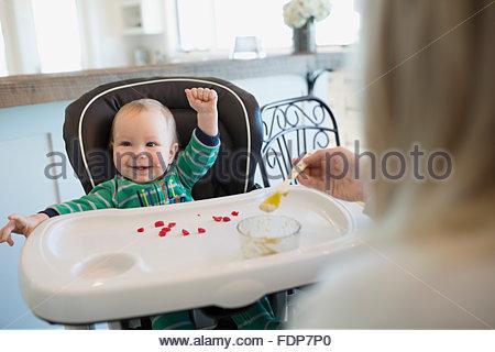 L'alimentation de la mère bébé garçon enthousiaste dans une chaise haute Banque D'Images
