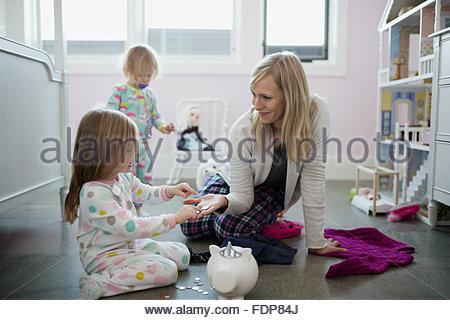 Mère et fille de placer les pièces en piggy bank Banque D'Images