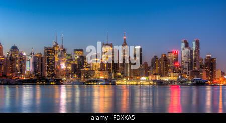 Le centre ville de Manhattan reste illuminé par des lumières qui se reflète sur la rivière Hudson avant le lever Banque D'Images