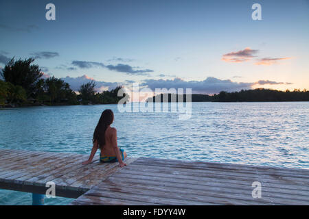 Woman sitting on jetty at sunset, Hauru Point, Mo'orea, îles de la société, Polynésie Française Banque D'Images