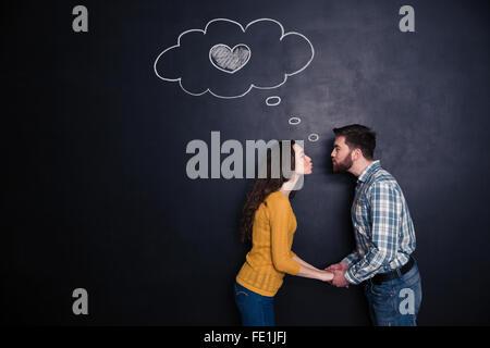 Heureux loving young couple holding hands et les baisers sur fond plaqué Banque D'Images