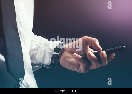 Les jeunes professionnels d'affaires méconnaissable texting on smartphone en utilisant app message bureau sombre Banque D'Images